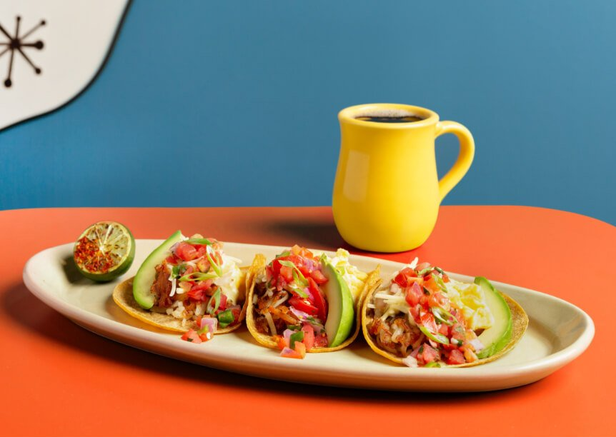 Snooze's Breakfast Tacos with Lime & Coffe On An Orange Tabletop