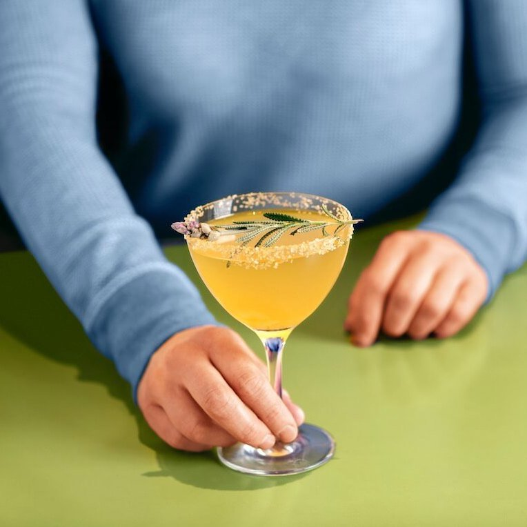 Woman in blue sweater holding the Snooze Abri-ca-lav-ra Mimosa; a combination of Snooze Sparkling, Apricot Liqueur, Fresh Lavender, Honey and Lemon Juice