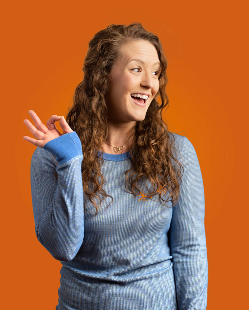A Snoozer In A Blue Shirt Smiling In Front Of An Orange Background