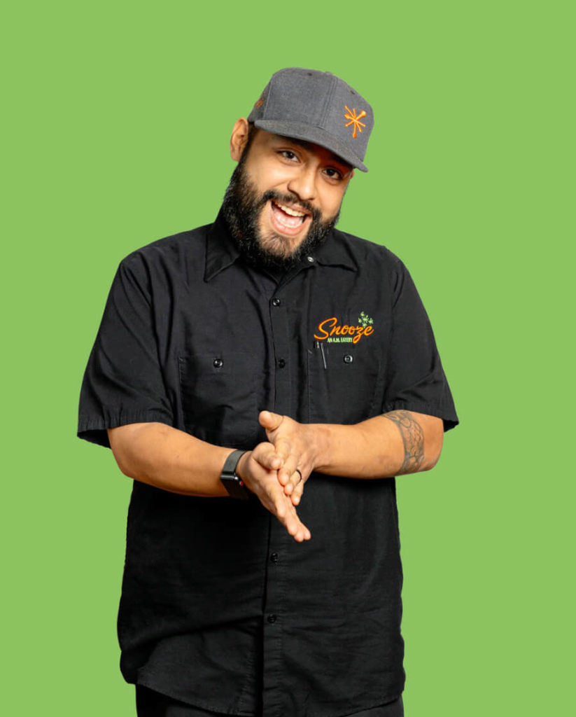 A Snoozer In A Black Chef's Shirt In Front Of A Green Background