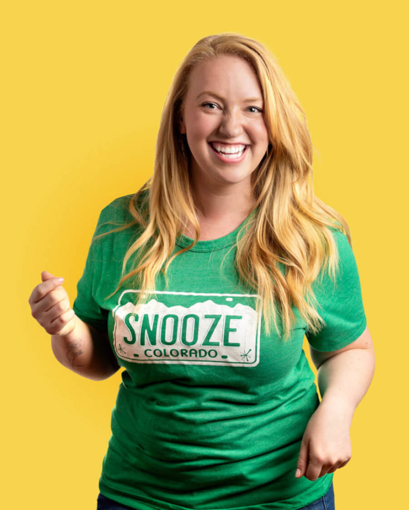 A Snoozer In A Green Colorado Snooze Shirt In Front Of A Yellow Background