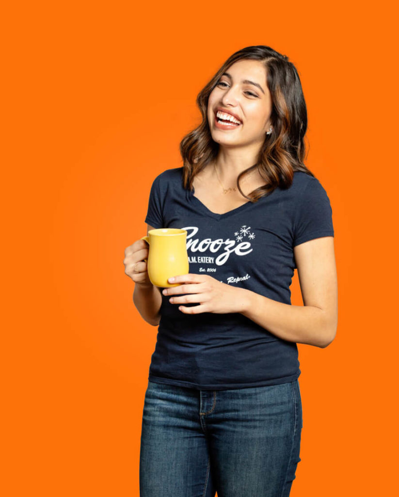A Snoozer In A Blue Shirt Holding Coffee In Front Of An Orange Background